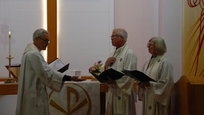 Bishop James Gonia of the Rocky Mountain Synod in Denver, left, conducts the installation of Pastor Christa von Zychlin and Pastor Wayne Nieminen to serve the Trinity Lutheran Church.