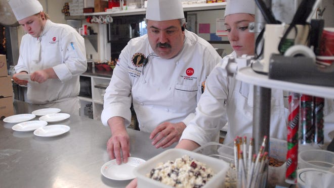 Chef Thomas Recinella, of the Baker College of Port Huron Culinary Institute of Michigan, assists student Calie Nelson as she prepares food for the Extravagant Love Café at Mid City Nutrition in Port Huron.