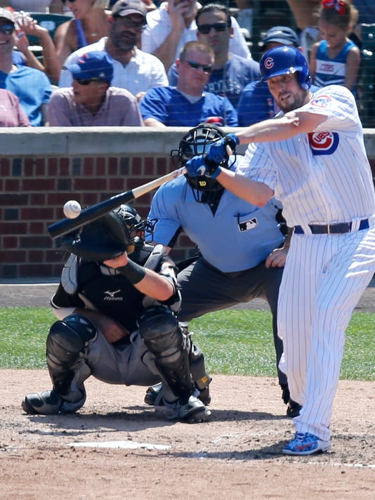Chicago Cubs' John Lackey hits his second double of the day off Miami Marlins starting pitcher Tom Koehler as catcher Jeff Mathis and umpire Marty Foster watch during the fifth inning of a baseball game Wednesday, Aug. 3, 2016, in Chicago. (AP Photo/Charles Rex Arbogast)