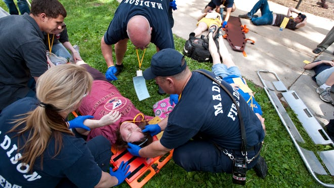 In this May 26, 2010 photo released by University of Wisconsin-Madison, members of the University Police Department, Madison Fire Department and other emergency personnel agencies triage wounded victims as they respond to a mock report of a suspect with a gun, bomb and hostages during a full-scale campus emergency response exercise at Bradley Hall at the University of Wisconsin-Madison, in Madison, Wis.  A fake bomb will be set off in or around Camp Randall stadium next week, as part of an emergency-response simulation that's one of the largest the state has ever seen. The exercise Thursday, July 17, 2014 near downtown Madison will involve more than 400 people from 20 agencies, and will test how well-prepared police, hospitals and first-responders are for a mass-casualty occurrence.(AP Photo/University of Wisconsin-Madison)