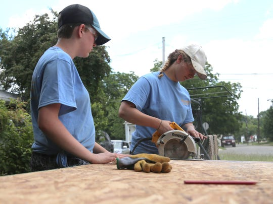 Haley Lambertson, 15, left, and Elizabeth Badertscher cut plywood for flooring at a home on Bowman Street as part of the Blue Rose Mission. Both girls hail from Aurora United Methodist Church and are helping out as part of church camp.