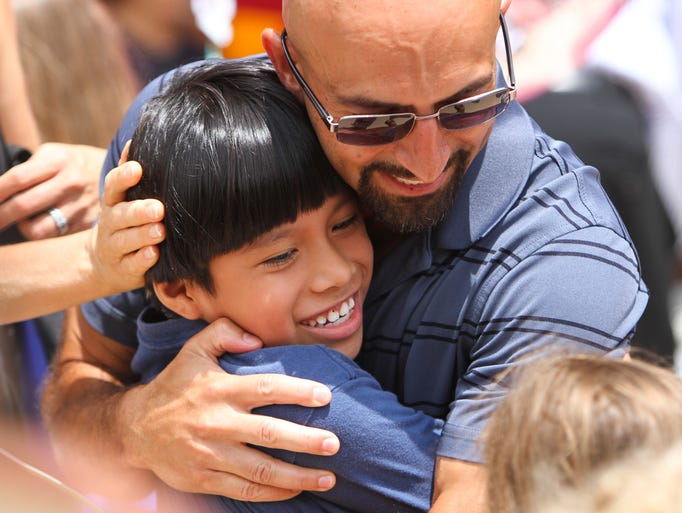 Morris Township, NJ - Michael Abadir hugs Leonel Garcia, the child he is hosting for the week. Children from New York City arrived in New Jersey today to meet their host families in the Fresh Air Fund Program, which allows city children to experience the outdoors during the summer.