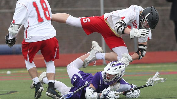 From bottom, John Jay's Dean Ford (21) gets pass off as he gets hit by Somers Jack Kessler (11) during boys lacrosse action at Somers High School April 1, 2017. John Jay won the game 15-5.