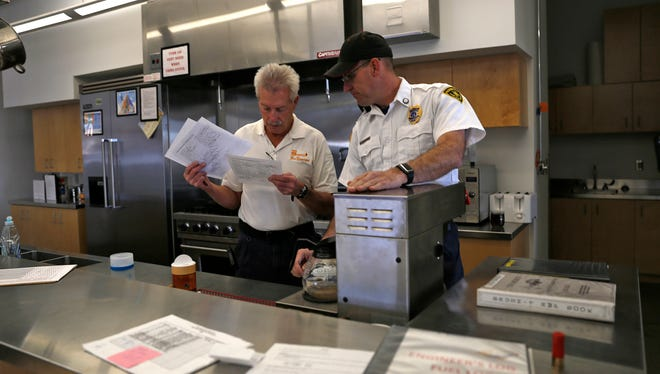 Bloomfield Fire Department Chief George Duncan, left, and Capt. Travis Olbert look over paperwork on March 4 before a safety meeting.