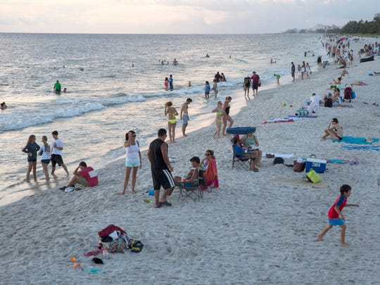 Tourists and locals take in the sunset over the Gulf of Mexico from the beach on Aug. 11, 2016, in Naples. The Southwest Florida tourism industry could face some negative effects in the face of a couple of months of tough press, with concerns such as Zika, algae and shootings occurring in our area.