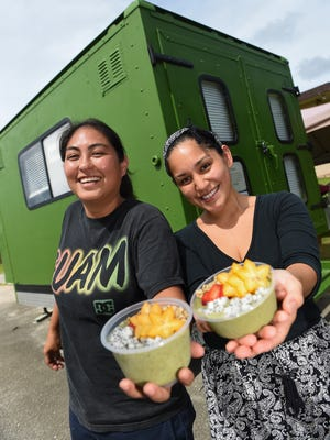 Z's Green Canteen co-owners Nikki Roberto, left, and Tonnie Guzman display their popular green smoothie bowl outside their food truck in Dededo on Aug. 7, 2017.