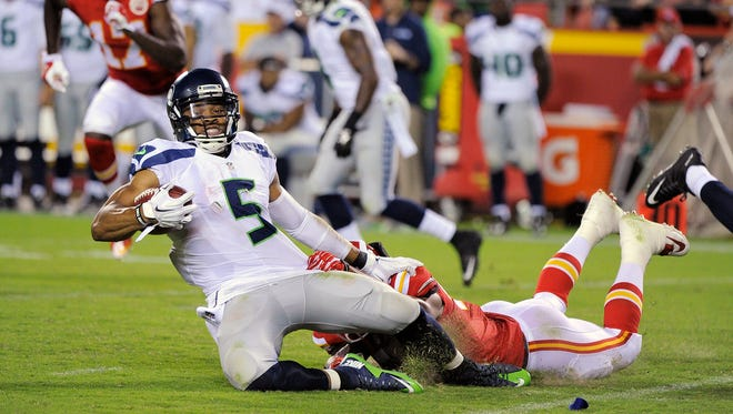 Seattle Seahawks quarterback B.J. Daniels (5) is tackled by Kansas City Chiefs linebacker D.J. Alexander (57) during the second half of a preseason NFL football game at Arrowhead Stadium in Kansas City, Mo., Friday, Aug. 21, 2015. The Chiefs defeated the Seahawks 14-13.