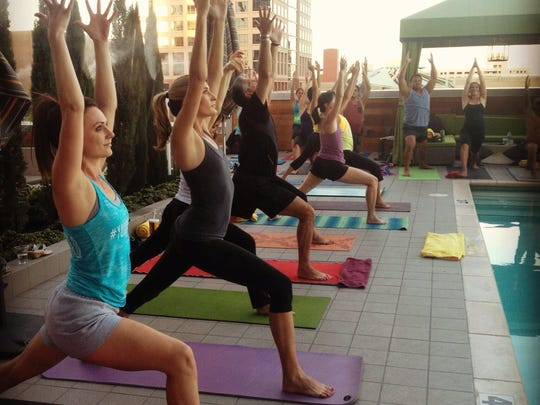 Participants do yoga by the pool at Lustre Rooftop Bar's summer yoga series.