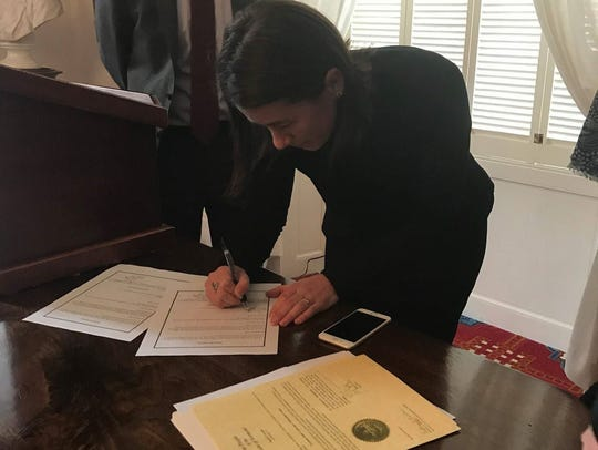 Sarah George signs papers at her swearing-in ceremony