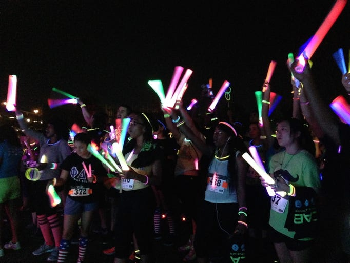 Runners wave their glow sticks at the Light the Knight