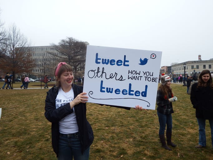 McCall Sarrett of Iowa City shows off her sign at the