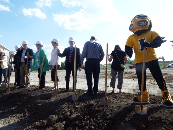 Herky the Hawk stands with local leaders at the groundbreaking