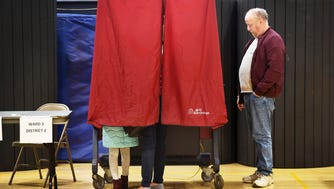 A woman accompanied by a young girl casts her vote at the Hackensack High School gym on Tuesday morning.