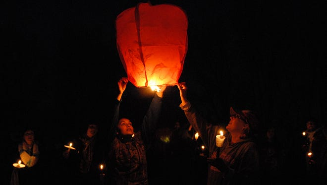 Elese Santus (left), the niece of Amy Santus, 33, of Perrysburg and the step-sister of Paige Widmer, 17, of Leesville, S.C., lights and releases a paper lantern in their memory during a vigil at Turtle Point Marina in Carroll Township on Friday April 25. Santus, Widmer, Santus' boyfriend Bryan Huff, 32, of Perrysburg, and Andrew Rose, 33, of Maumee, perished in a boating accident in the area on Lake Erie on April 16.