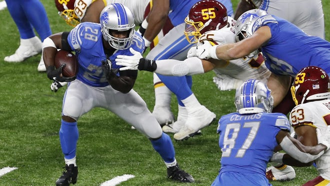 Detroit Lions running back Adrian Peterson (28) runs the ball against Washington Football Team linebacker Cole Holcomb (55) during the third quarter Nov. 15 at Ford Field in Detroit. The Lions will face the Houston Texans at 11:30 a.m. Thursday to kick off the Thanksgiving Day slate of NFL games. The game will air on CBS. Washington will face Dallas at 3:30 p.m. on FOX.