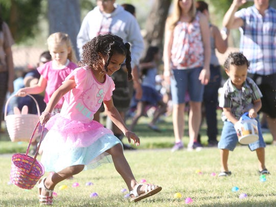 "5-year-old Kamia Haltom runs to gather ""eggs"" during the Palm Springs Firemen's Association Easter egg hunt at Ruth Hardy Park in Palm Springs on Saturday."