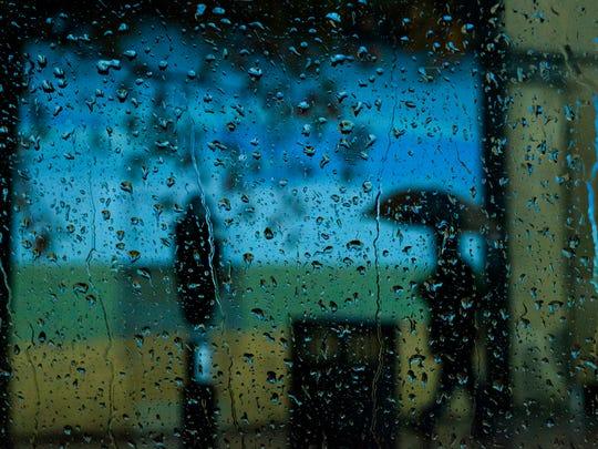 Pedestrians walk through the rain on Monday, Dec. 5,