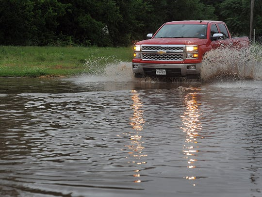 A pickup powers through a large puddle Friday in Wichita