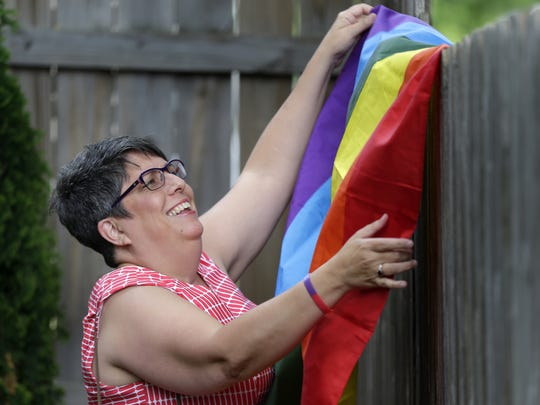 Kathy Flores, Appleton's diversity coordinator, hangs a rainbow flag at a celebration following the U.S. Supreme Court's historic ruling on same-sex marriage in June 2015.