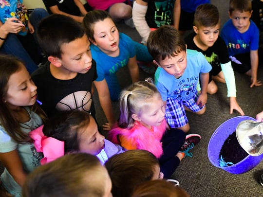 Kids watch a asian scorpion glow under a ultraviolet light during a Creepy Critters animal show by Animal Tales at the Henderson County Public Library Tuesday, October 11, 2016.