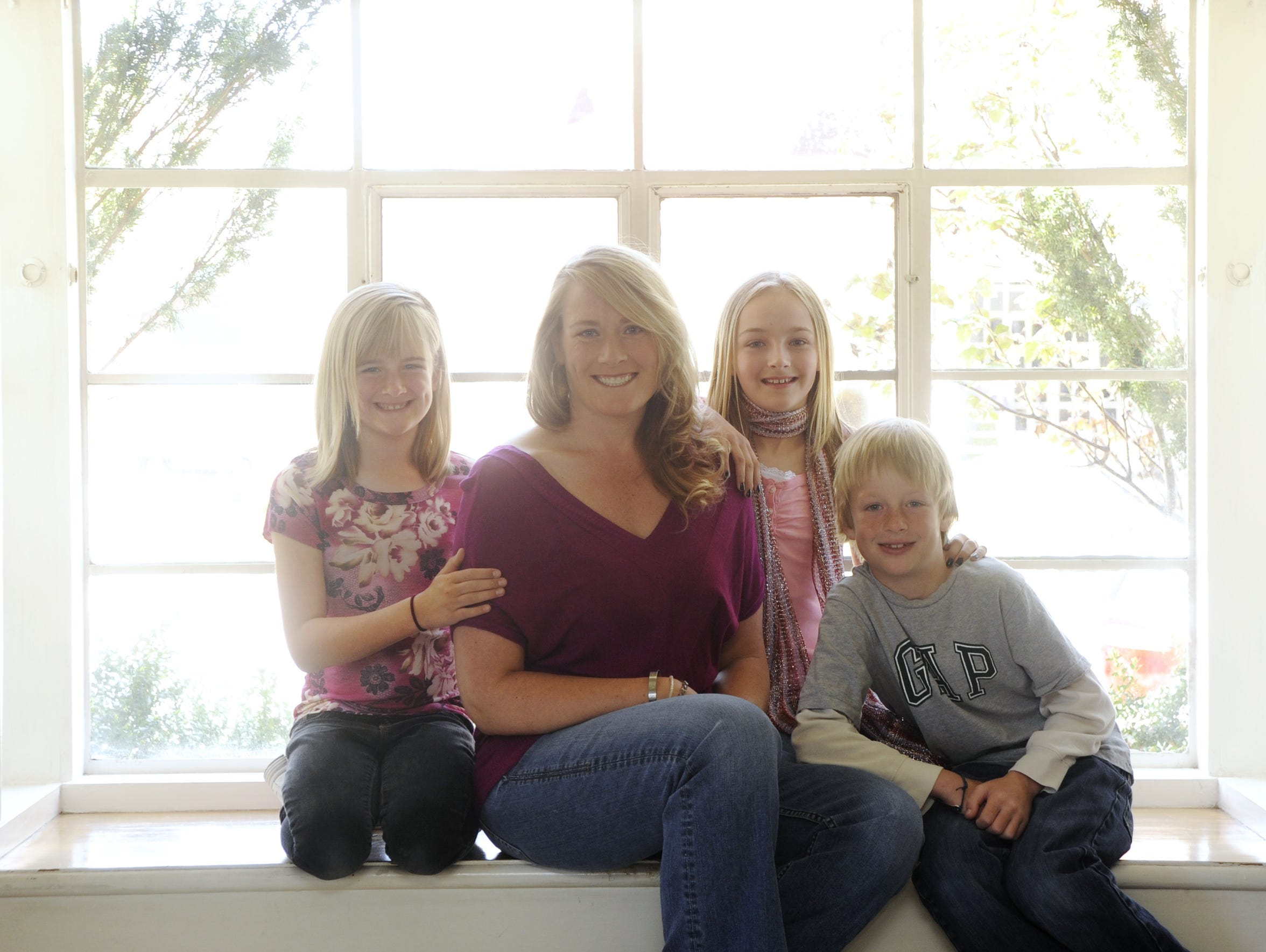 Emily Reese of Reno sits with her children Kate, 9,