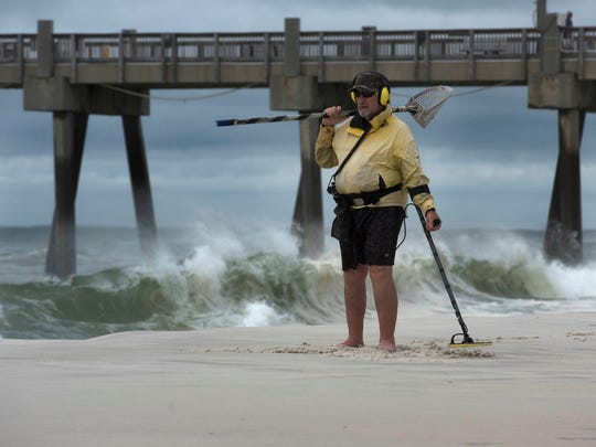 Kelly Overholser searches for treasure washed ashore on Pensacola Beach as Subtropical Storm Alberto approaches on Monday.