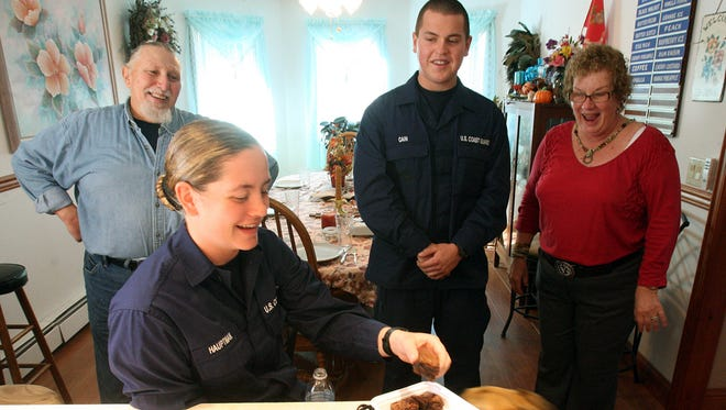 In this Thursday Nov. 22, 2012, file photograph, U.S. Coast Guard Training Center recruits Mary Hauptman, of Alaska, second left, and John Cain, of Missouri, second right, enjoy snacks at the host family home of Jay Jordan, left, and Marylou Jordan, right, of Lower Township, N.J.