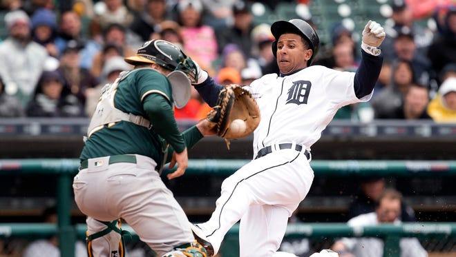 Detroit Tigers' Anthony Gose slides safely past the tag of Oakland Athletics catcher Stephen Vogt on a Ian Kinsler double in the third inning of a baseball game in Detroit, Thursday, April 28, 2016.