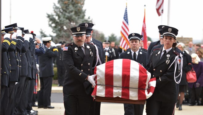 Hamilton Fire Color Guard carries their fellow firefighter into the church. Services are held for fallen Hamilton firefighter Patrick Wolterman, 28, December 31 at Princeton Pike Church of God in Maustown, in Liberty Township.