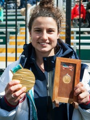 UVM alum and Vermont native Amanda Pelkey shows off her gold medal from this years Olympic games next to Albert Gutterson's gold medal from 1912 during the men's lacrosse game between there UMass Lowell Riverhawks and the Vermont Catamounts at Virtue Field on Saturday afternoon April 7, 2018 in Burlington. (BRIAN JENKINS/for the FREE PRESS)