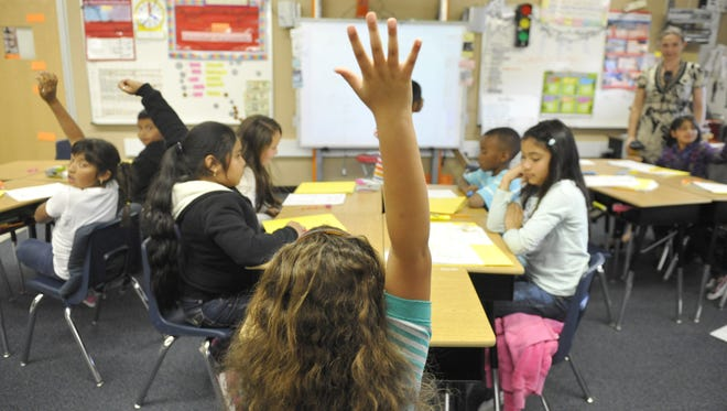 Third grade students at Maxwell Elementary School raise their hands to answer a question.