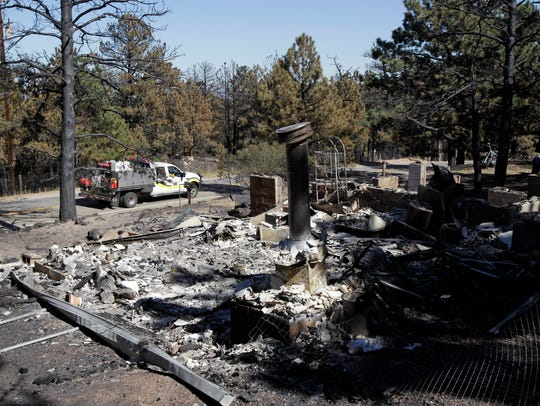 A firetruck drives past a home destroyed by the Fourmile