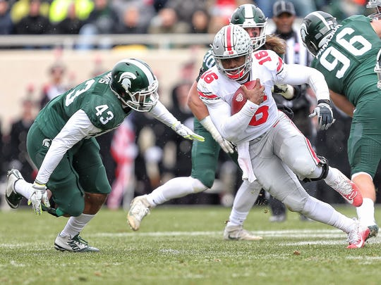 Ohio State quarterback J.T. Barrett tries to elude the grasp of Michigan State linebacker Ed Davis.