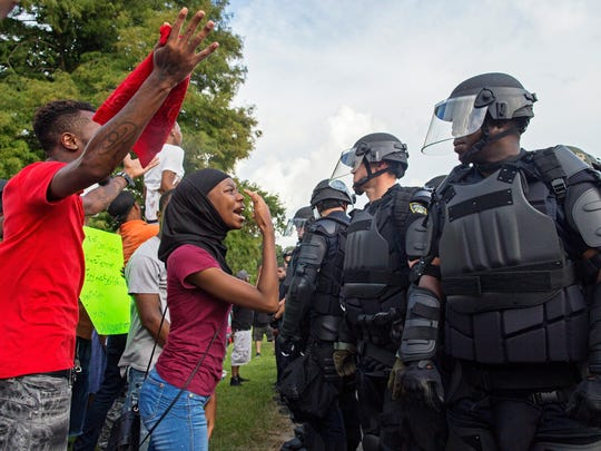 A protester yells at police officers in riot gear after being forced off the motor way in front of the the Baton Rouge Police Department Headquarters in Baton Rouge, La., Saturday, July 9, 2016. Several hundred protesters, including members of the New Black Panther party, blocked the road causing police to close the road and move the crowd with riot police. (AP Photo/Max Becherer)