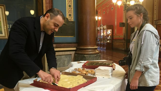Dr. Bilal Kaaki of Cedar Falls, a native of Lebanon, cuts a piece of manakish, a type of flatbread, for Emily Rizvic, 16, of Des Moines, a student at Lincoln High School, on Tuesday at the Iowa Capitol. They were participating in Iowa Muslim Day activities.