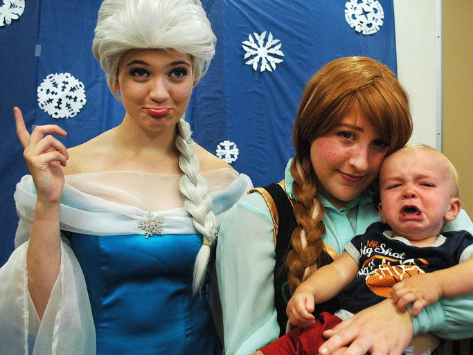 """Wilson Guy, 11 months, of Hendersonville was a little scared of Queen Elsa (left) of Arendelle and Princess Anna at the """"Frozen"""" event at the Gallatin Public Library on Thursday."""