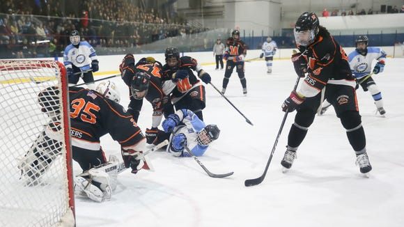 Suffern's Kyle Foresta (21) is taken down in front of the Mamaroneck goal during the second period of ice hockey action at Sport-O-Rama in Suffern on Friday, January 12, 2018.