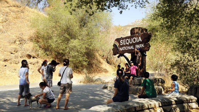 Visitors take photos in the foothills area of Sequoia National Park.