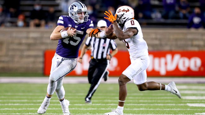 Kansas State freshman quarterback Will Howard (15) stiff-arms Oklahoma State cornerback Christian Holmes (0) during their Nov. 7 game at Bill Snyder Family Stadium in Manhattan.