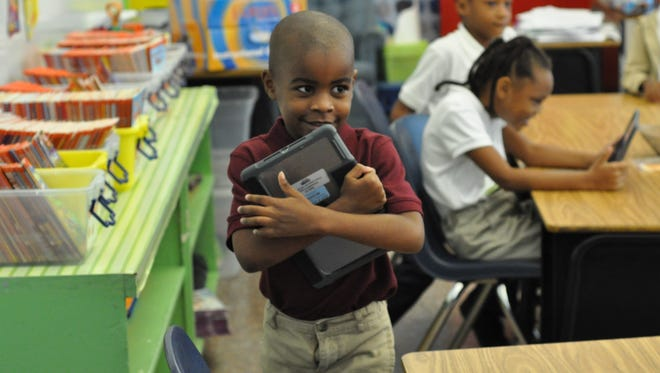 W.O. Hall second-grader Jeremiah Noel walks back to his seat after receiving an iPad in class Friday morning.