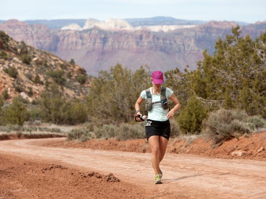 Suzanne Lewis competes in the Zion 100 ultra marathon trail race as she makes her way towards Gooseberry Mesa near the 50 mile mark on the course Friday, April 19, 2013. Runners began the day at 6am at the town park in Virgin and spent hours racing to the tops of mesas and back down over either a 100 mile or a shorter 100 kilometer course during the race.