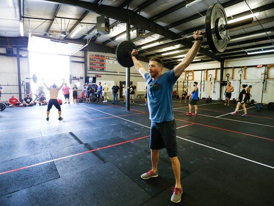 CrossFitter Brett Holmes lifts weights above his head