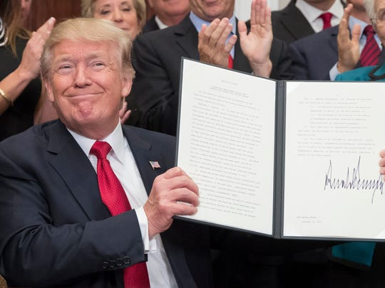 US President Donald J. Trump holds up an executive order on healthcare after signing it during a ceremony in the Roosevelt Room of the White House in Washington, DC, USA, 12 October 2017. The executive order overhauls federal regulations of the health insurance market, encouraging insurance companies to create cheap plans. Critics of the plan say that it could draw away young and healthy people from the markets created by the Affordable Care Act.