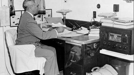 In this Aug. 6, 1945,  photo aboard the cruiser USS Augusta, President Harry Truman, with a radio at hand, reads reports of the atomic bomb raid of Hiroshima, Japan, while en route home from the Potsdam Conference.