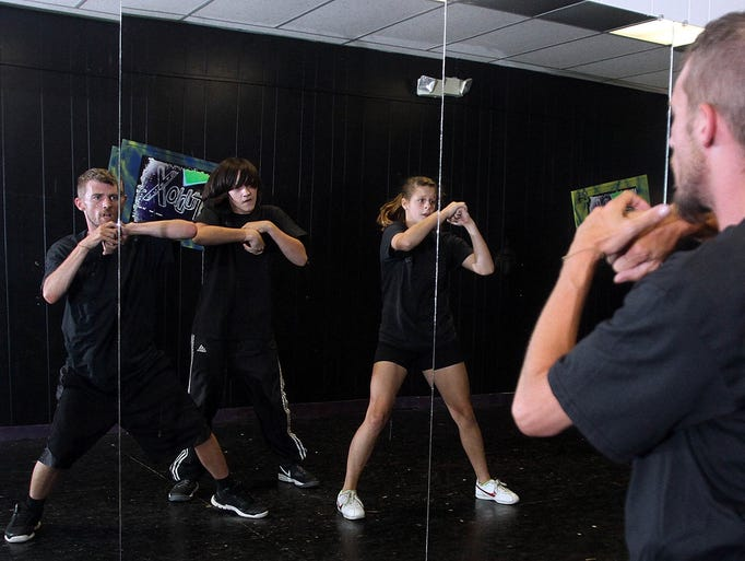"""Studio X dancers Kenny Creviston (left) Johnny Workman and Paiton Bonsel perform their original dance """"C' N Red"""" in a mirrored studio room at 129 S. Main St. in preparation for a performance at Downtown Marion Christmas in July scheduled for tonight in Busby Park. James Miller/The Marion Star"""