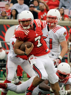 Louisville sophomore quarterback Reggie Bonnafon (7) breaks the tackle of Isaac Stewart (42) on a run from scrimmage in the annual spring football scrimmage game at Cardinal Stadium in Louisville, Ky.