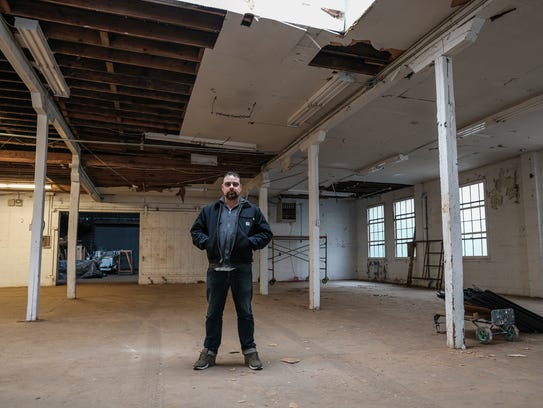Jesse Cory, CEO of 1xRun, stands in a warehouse space in Detroit that will be the new location of the printmaker. The arts business and affiliated Inner State Gallery will be leaving their building near Eastern Market, which was sold for $1.2 million as part of the plan to move to a larger facility near the Heidelberg Project in Detroit.