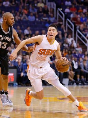 Phoenix Suns guard Devin Booker (1) works against San Antonio Spurs center Boris Diaw (33) in the first half of their NBA game Sunday, Feb. 21,  2016 in Phoenix, Ariz.