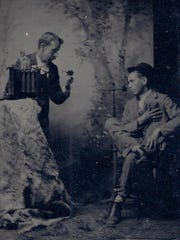 William Daugherty, a photographer in Milford beginning around 1894 is pictured here photographing an unknown subject in his studio.