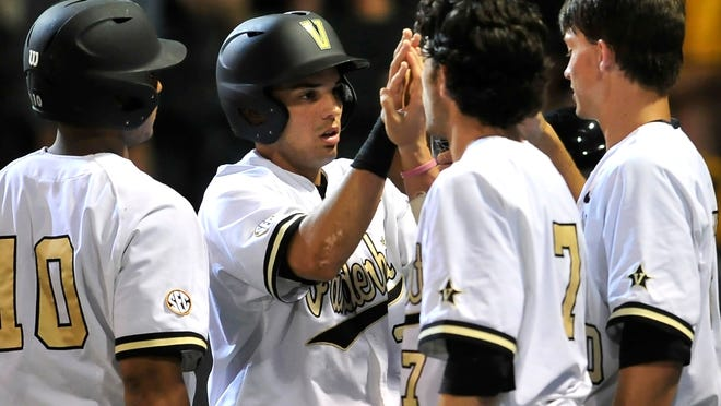 Vanderbilt's Vince Conde, second from left, is congratulated by teammates after scoring a run against Xavier in the fourth inning Friday in the Nashville Regional at Hawkins Field.